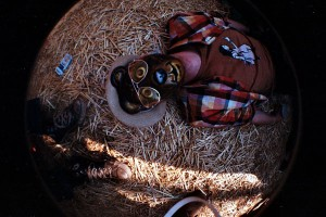 A man wearing a bear mask passed out on the grass during Oppikoppi 2010.